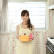 Japanese girl with a pan in the kitchen - Stock Photo