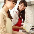 Japanese girls washing dishes in the kitchen — Stock Photo