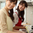 Japanese girls washing dishes in the kitchen - Stock Photo