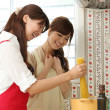 Japanese girls cooking in the kitchen - Stock Photo