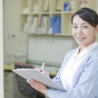 Japanese nurse in examination room with medical records - Stock Photo