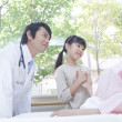 Japanese inpatient with doctor and hospital visitor - Stockfoto