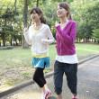 Two women jogging in a park - Stock Photo