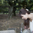 Woman drinking from fountain in Park - Stock Photo