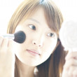 Woman applying make-up with brush - ストック写真