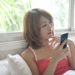 Woman text messaging on cell phone - Stock Photo