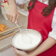 Woman mixing flour in a bowl - Stock Photo