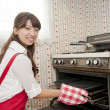 Woman operating oven - Stock Photo