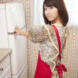 Woman opening refrigerator in a kitchen — Stock Photo