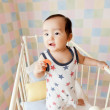 Baby girl standing in crib - Stock Photo