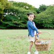 Girl holding picnic basket in a field - Stock Photo