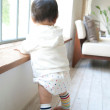 Baby girl learning to walk with window support - Stock Photo