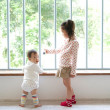 Two children standing at a window - Stock Photo