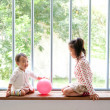 Two children playing on window sill - Stock Photo