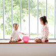 Two children playing on window sill - Foto de Stock