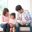 Girl reading a book with her parents - Stock Photo