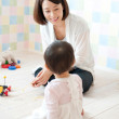 Baby girl playing with her mother - Stock Photo