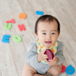 Baby boy playing on wooden floor - Stock Photo