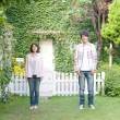 Young couple standing in a lawn smiling - Stock Photo