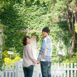 Young couple standing with holding hands in lawn — Foto de Stock