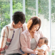 Young couple with their baby girl sitting on a window sill - Stock Photo