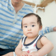 Baby girl sitting with her father holding a book - Stock Photo