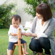 Mother with her daughter on toy rocking horse in a domestic garden - Stock Photo