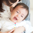 Woman holding a crying baby in her lap - Stock Photo