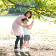 Woman with her daughter holding a branch of a tree - Stock Photo