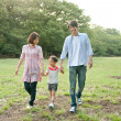 Family walking with holding hands in a park - Stock Photo