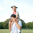 Young man carrying his daughter on shoulders - Stock Photo