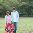 Young couple walking with baby in pushchair - Stok fotoğraf