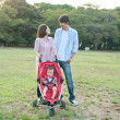 Young couple walking with baby in pushchair - Stock Photo