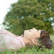 Young woman lying in grass - Foto de Stock