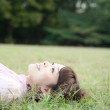 Young woman lying in grass - Stock Photo