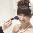 Bride getting makeup applied to face - Stockfoto