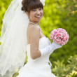 Bride holding a bouquet smiling - Stock Photo