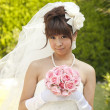 Bride holding a bouquet and smiling - Stock Photo