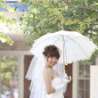 Bride holding an umbrella and smiling - Stockfoto