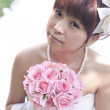 Mid section view of a bride holding bouquet of roses - Stock Photo