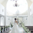 Bride walking in aisle lined with flowers in empty church - Stock Photo