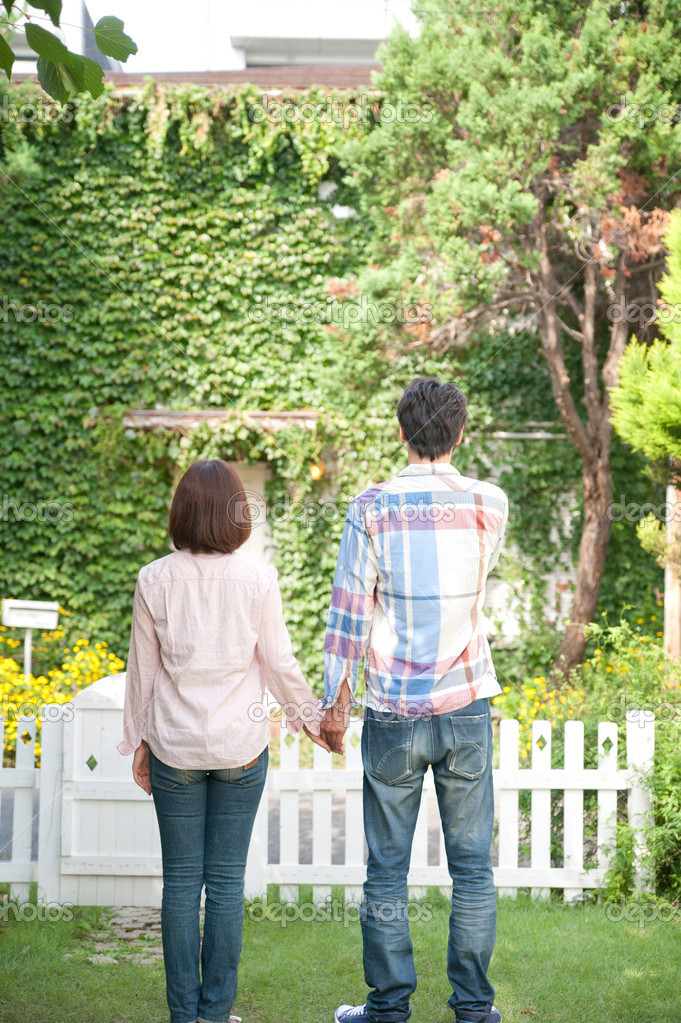Rear view of a couple standing with holding hands in lawn — Stock Photo #19624591