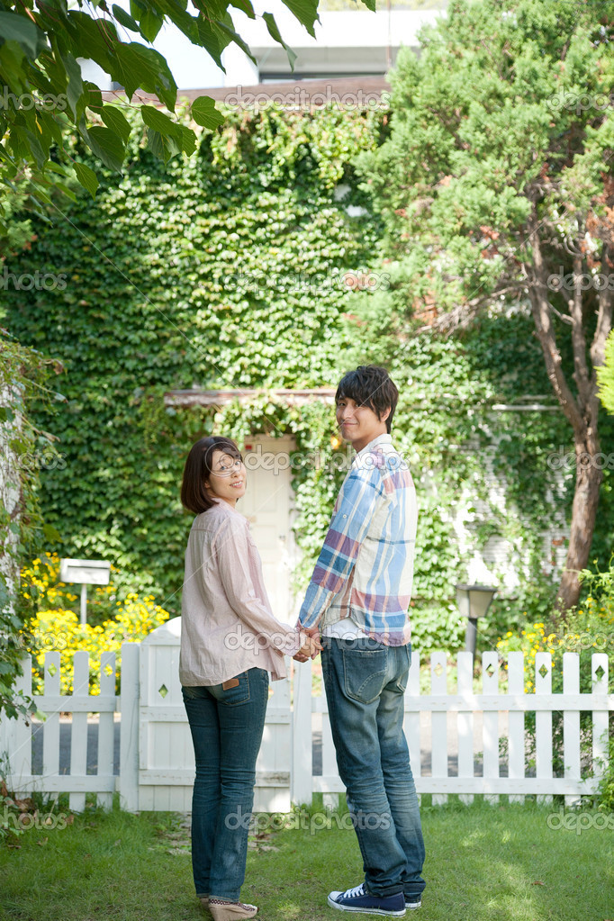 Young couple standing with holding hands in lawn  Stock Photo #19624673
