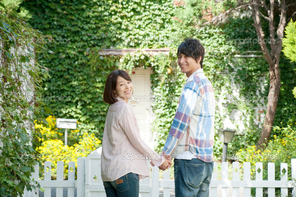Young couple standing with holding hands in lawn — Stock Photo #19624689