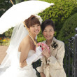 Bride with her mother standing under an umbrella - Stock Photo