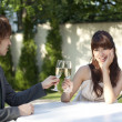 Young couple toasting with champagne at outdoor table - Stock Photo