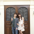 Young couple standing at the front door of a house - Stock Photo