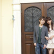 Young couple standing at the front door of a house - Stok fotoğraf