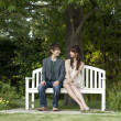 Young couple sitting on a bench in a garden - Foto Stock