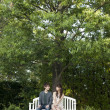 Young couple sitting on a bench in a garden - Stock Photo